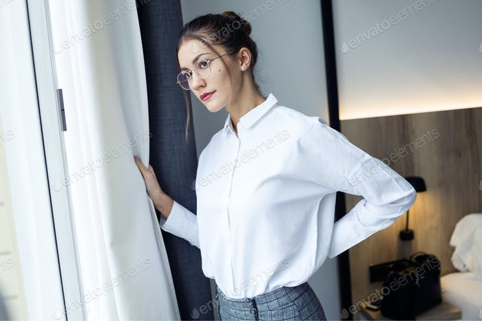 Confident young businesswoman looking sideways standing near the