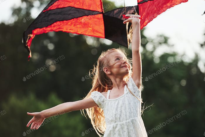 Good wind. Happy girl in white clothes have fun with kite in the field. Beautiful nature