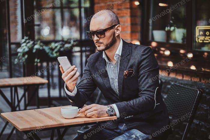 Привлекательный элегантный бизнесмен сидит в кафе