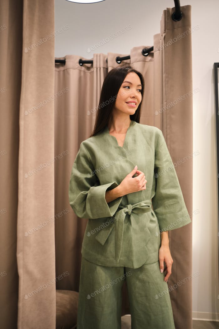 Attractive Asian girl trying on stylish suit dreamily looking away in dressing room of clothes store