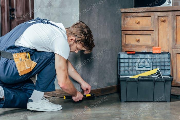 professional young foreman hammering nail into baseboard