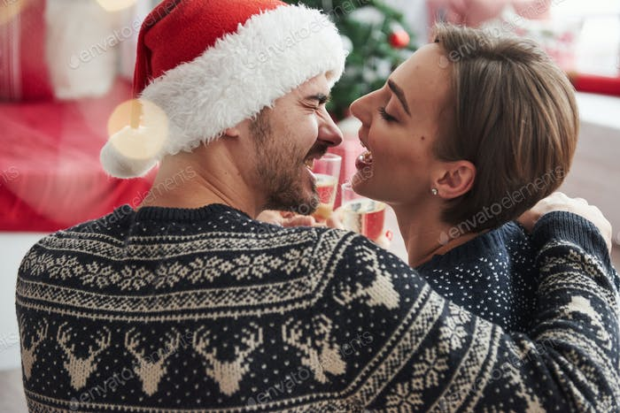 Knocking glasses. Beautiful couple in holiday clothes sits and hugs each other. Photo from the back