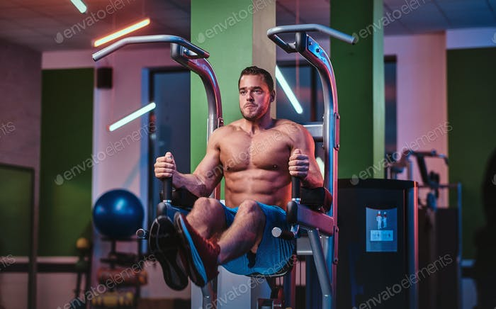Shirtless bodybuilder in a modern fitness club