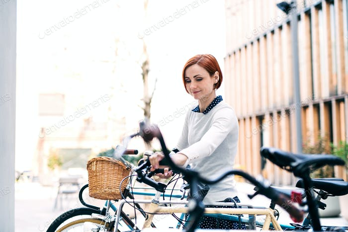 A young business woman with bicycle standing outdoors