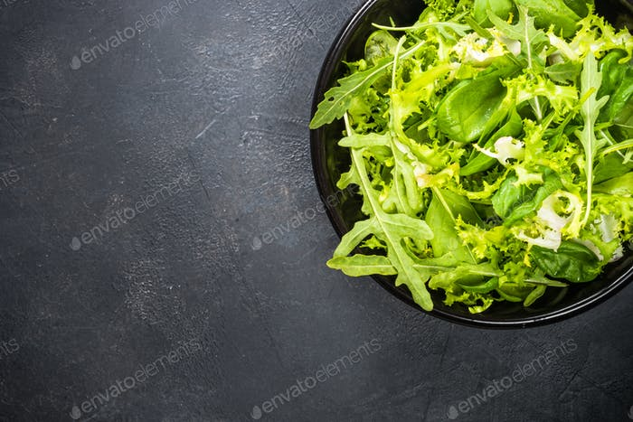 Green salad leaves mix on black top view