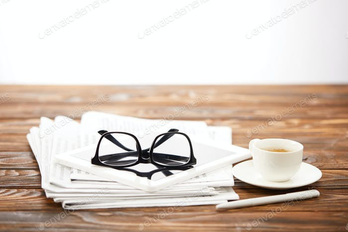 eyesight, cup of coffee, digital tablet and pile of newspapers on wooden surface