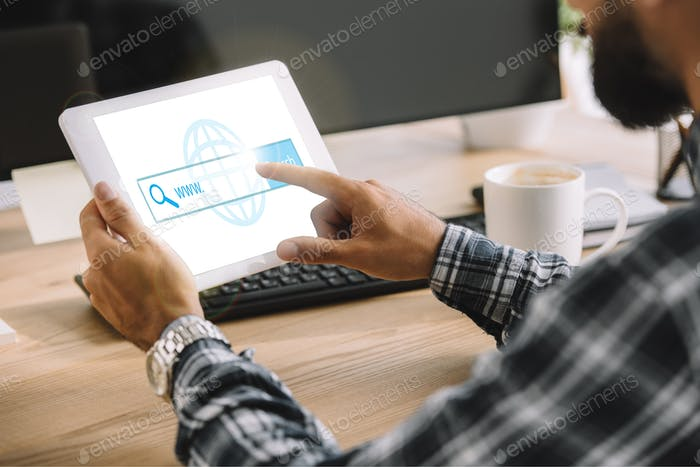 cropped shot of seo manager using tablet with website on screen