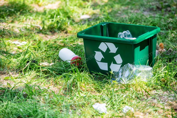 recycling box and plastic trash on green grass