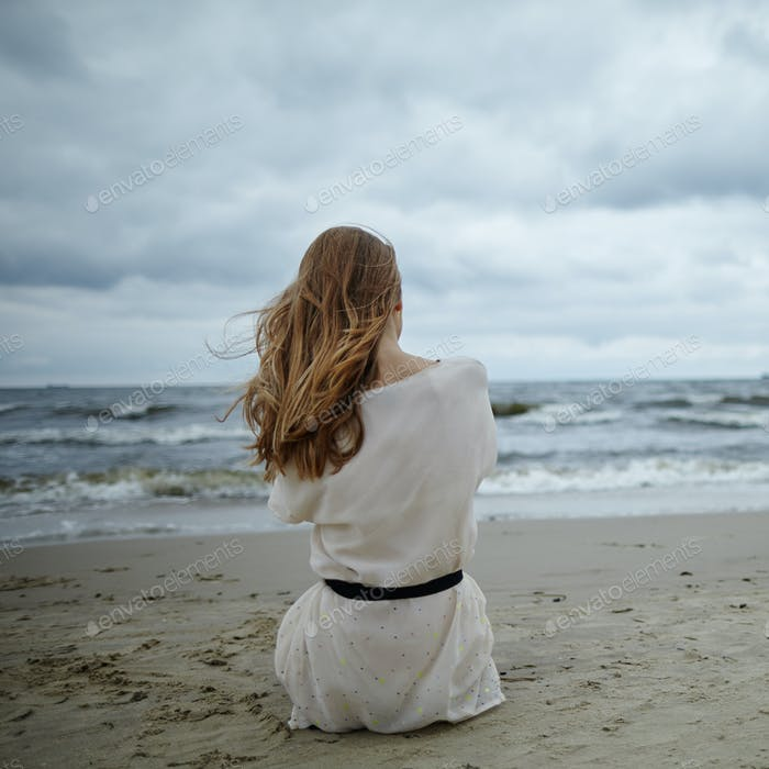 young beautiful woman on cold windy beach