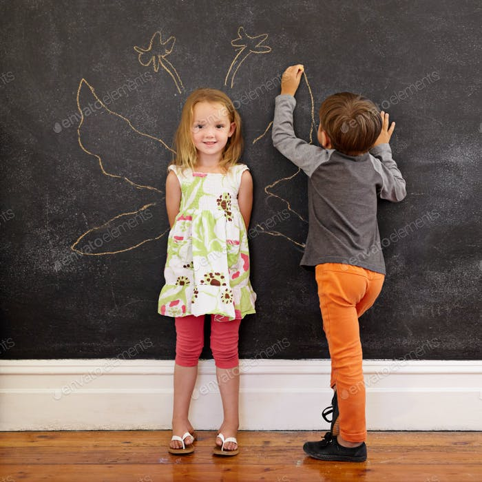 Little girl in front of a blackboard with boy drawing angel wing