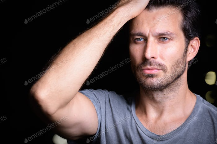 Face of handsome bearded man brushing hair back outdoors at night