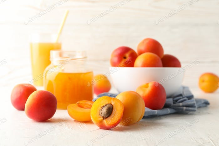 Composition with apricots, juice and jam on white table