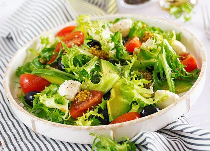 Frischer Salat mit Avocado, Tomaten, Oliven und Mozzarella in einer Schüssel. fitness-essen Vegetarisches Essen.