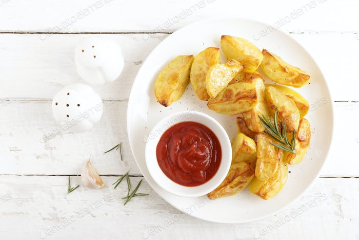 Potato baked and tomato ketchup on white plate, wooden background, top view
