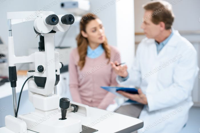 oculist and patient in clinic with slit lamp on foreground