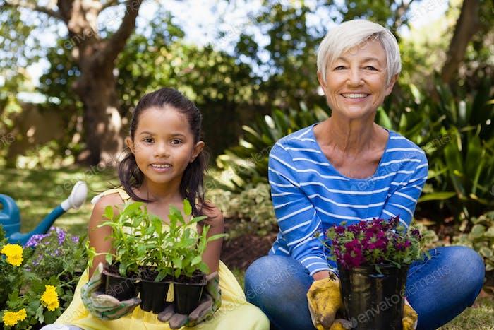Porträt lächelnd Mädchen und Enkelin sitzen, während Pflanzen halten