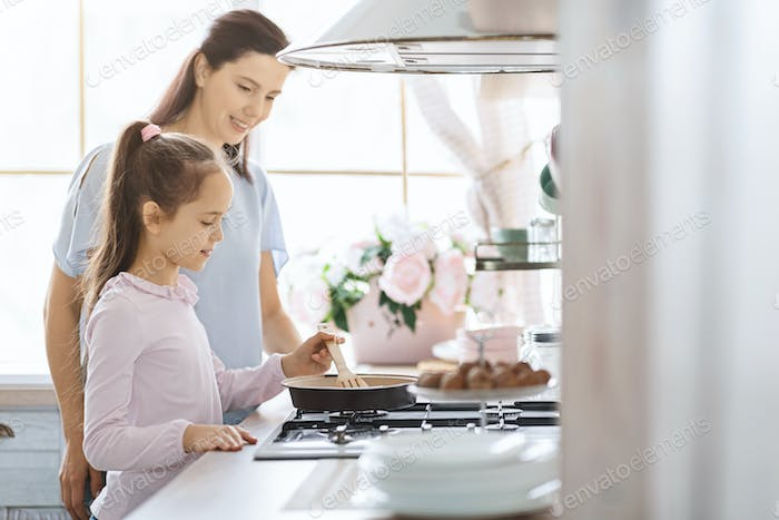 Little girl learning how to cook under supervision of mother