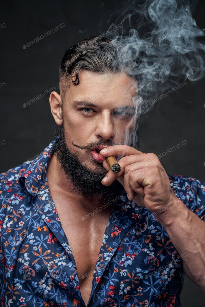 Muscular macho smoking cigar and posing in gray background