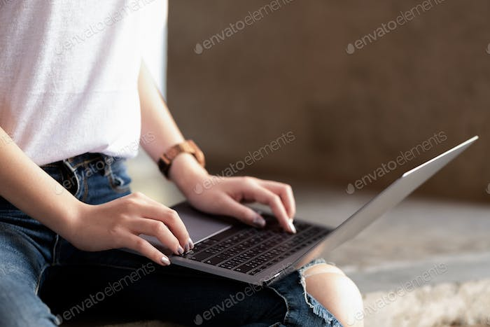 Young women using laptop on the leg.