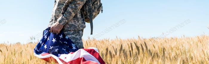 panoramic shot of patriotic soldier in military uniform holding american flag while standing in