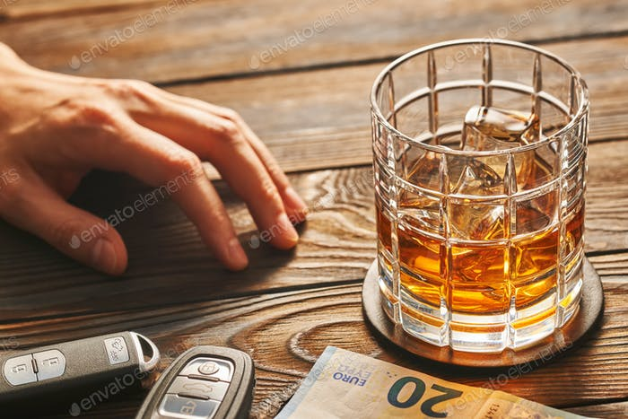 Man's hand reaching to glass with alcohol drink and car key. Drink and drive concept.