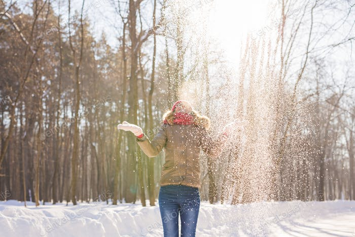 Beauty Girl Blowing Snow in frosty winter Park. Outdoors. Flying Snowflakes.