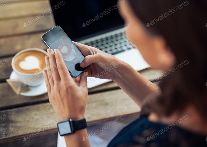 Woman taking photo of coffee with smartphone