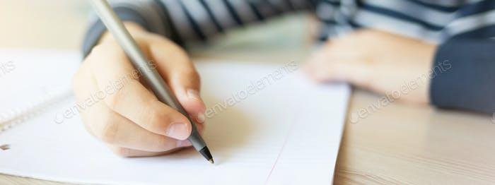Kid Writing in Notizbuch.
