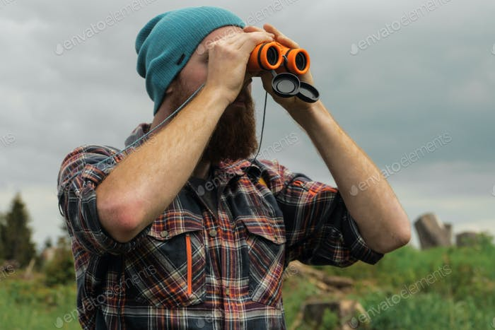 male hiker using binoculars outdoors