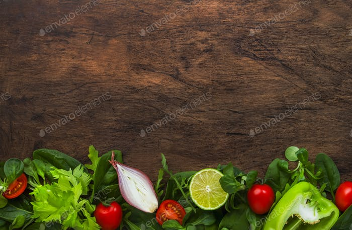 Healthy food background with various green herbs and vegetables.