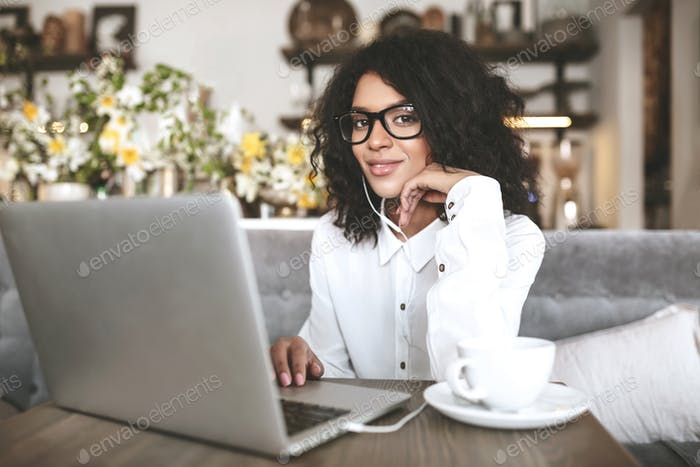 Young lady with dark curly hair working on laptop in earphones