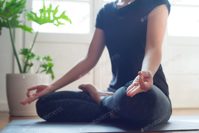 Woman doing yoga in the morning at her home.