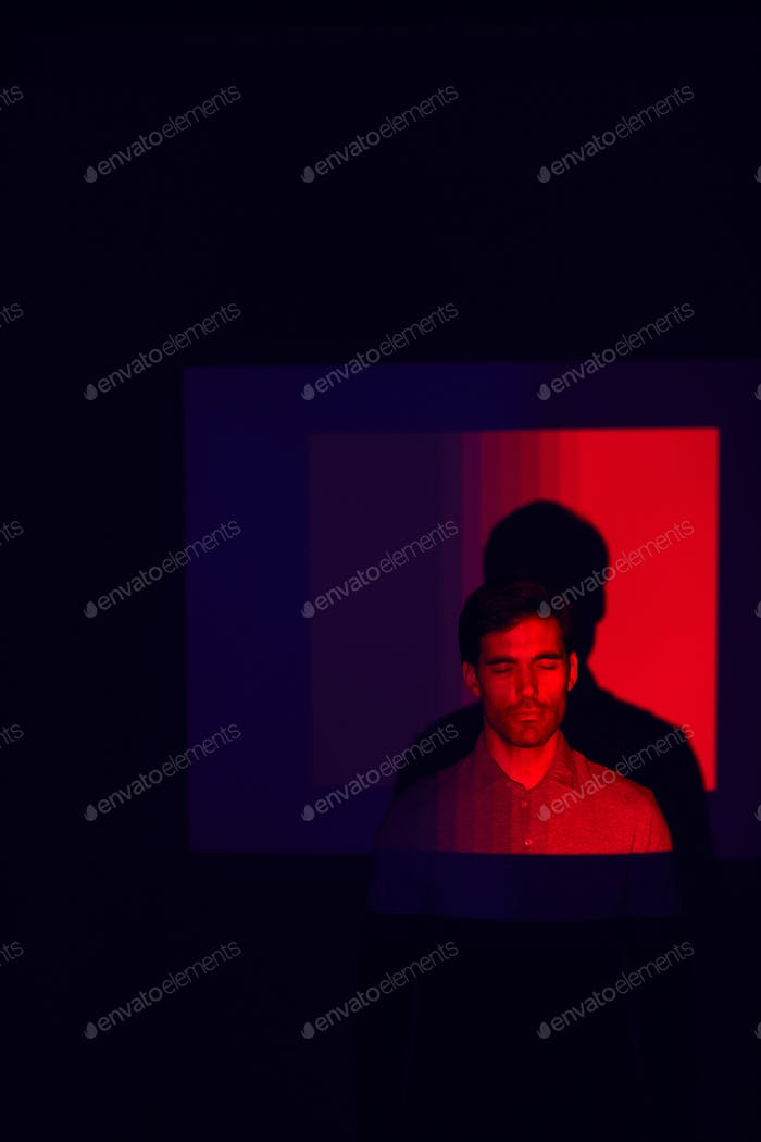 Studio Shot Of Man With Eyes Closed Illuminated By Red Light