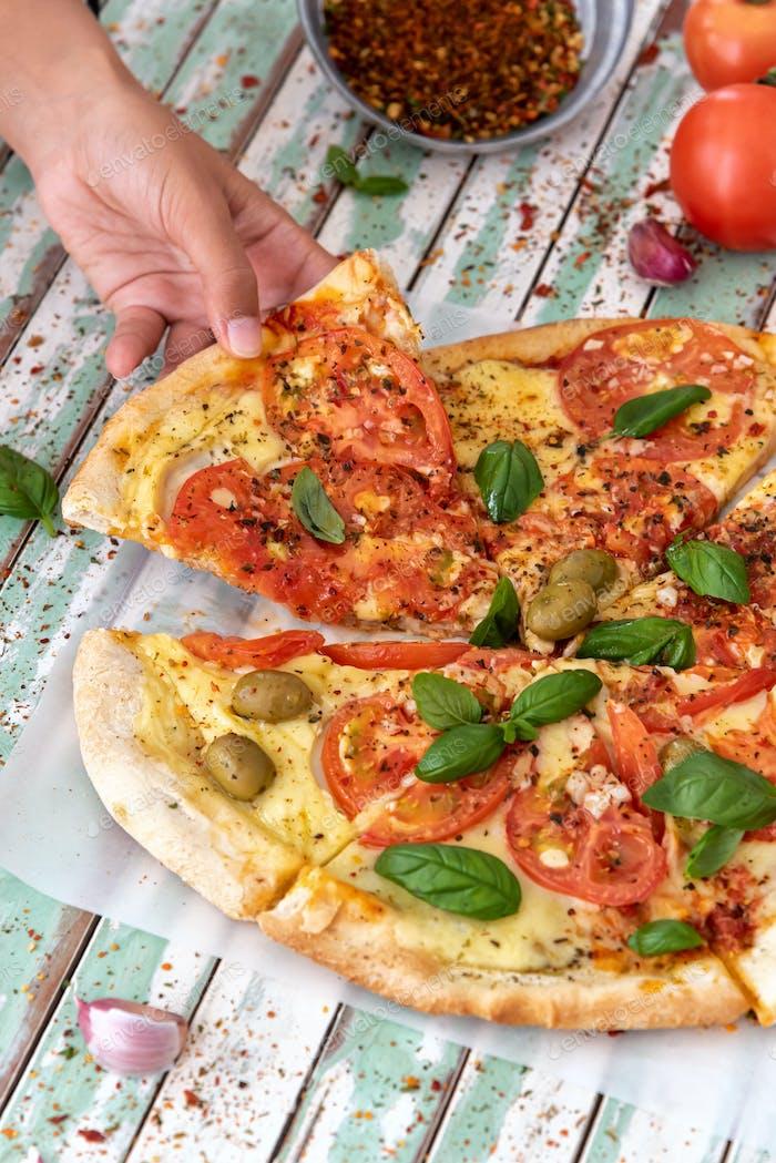 Hand einer Frau, die eine Scheibe einer Pizza von oben betrachtet