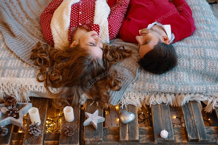 Young couple laying on the bed smiling with heads upside down