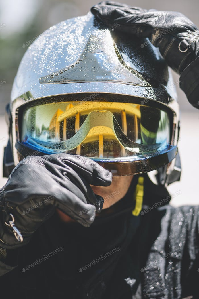 Firefighter poses with helmet looking at camera.