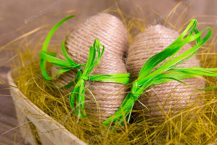 Easter eggs wrapped in twine in yellow nest