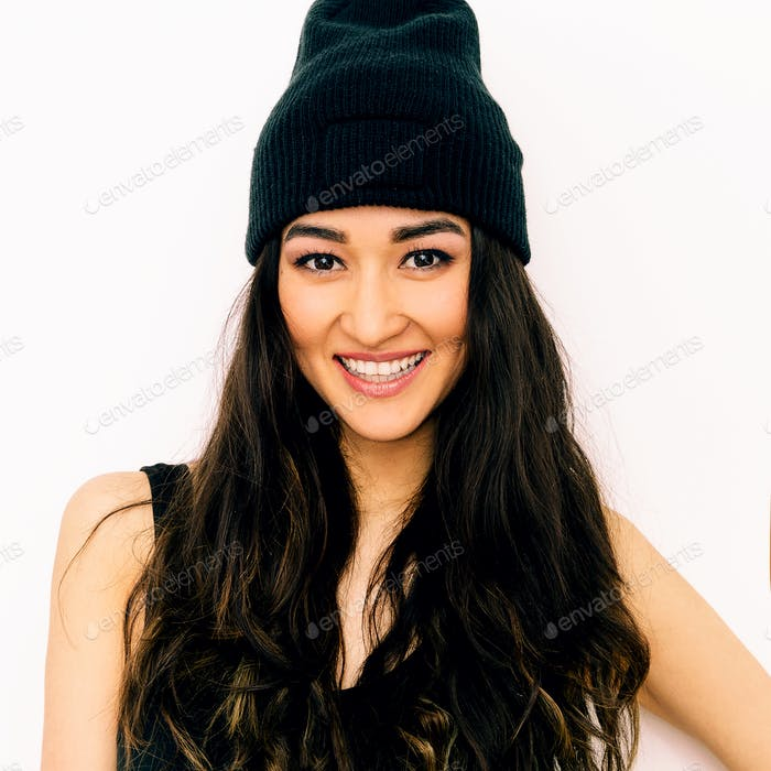 Happy brunette Girl in black clothing and beanie cap. Swag style