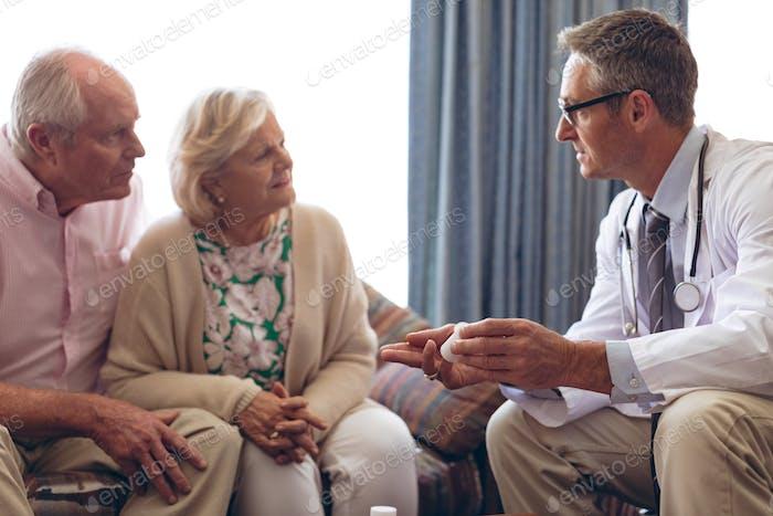 Male doctor prescription medicine to senior Caucasian couple at retirement home