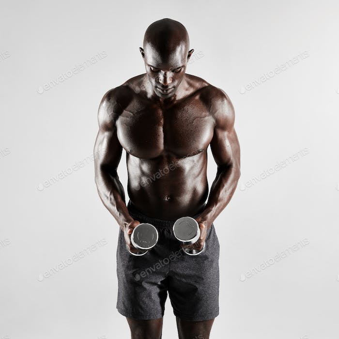 Muscular male fitness model holding dumbbells