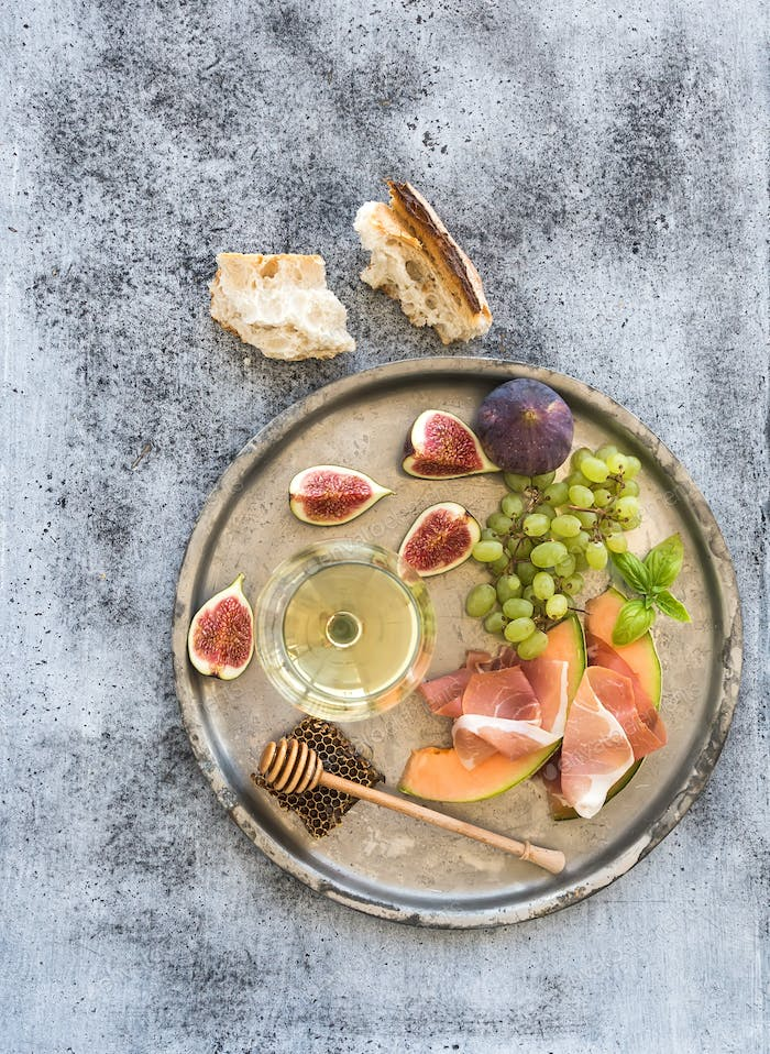 Glass of white wine, honeycomb with drizzlier, figs, grapes, melon and prosciutto
