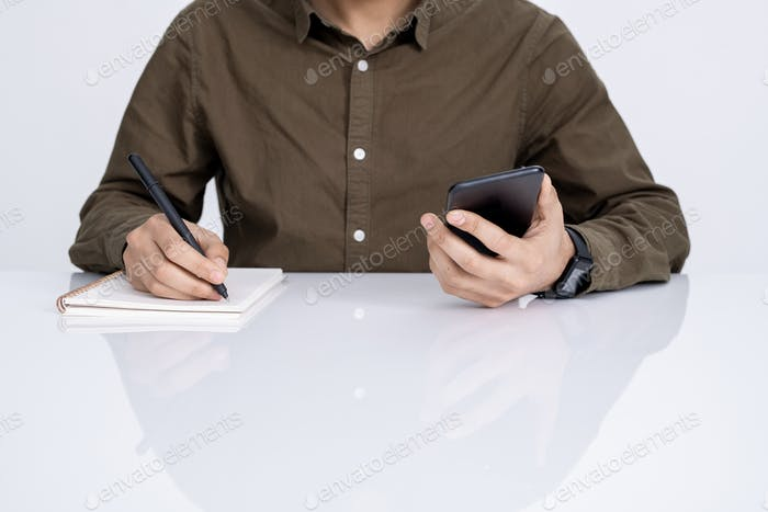 Hands of young businessman with smartphone and pen writing down working plan