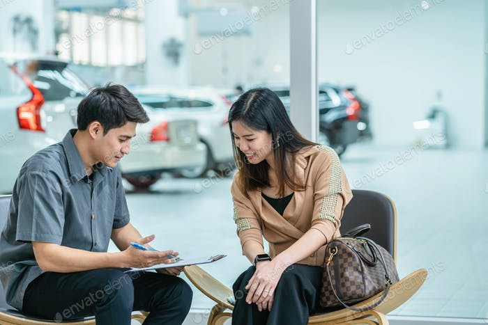 Азиатский механик, объясняющий контрольный список обслуживания клиенту в выставочном зале