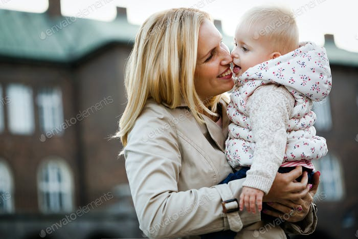 Happy mother and baby kissing, laughing and hugging in nature outdoors