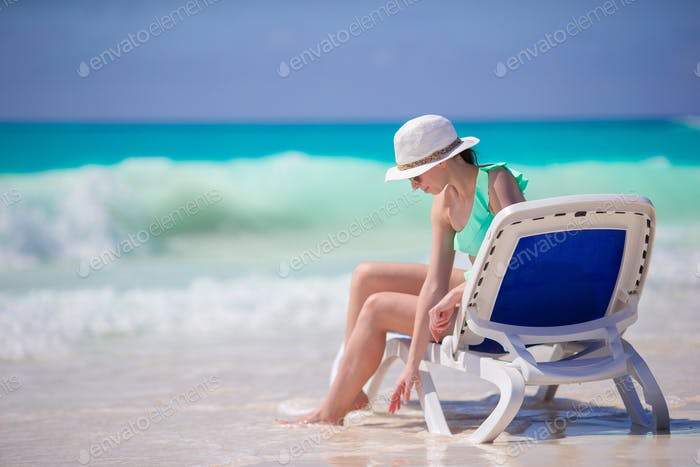 Young woman in hat on a tropical beachrelaxing in lounger