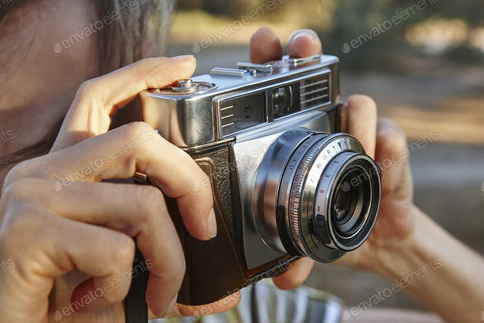 Woman taking pictures with vintage camera. Travel background. Vacation