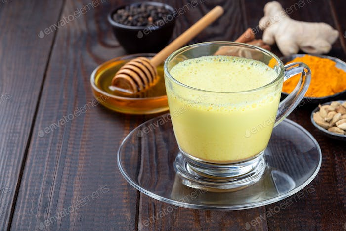 Moon milk with turmeric in glass cup, ingredients on background, horizontal, copy space