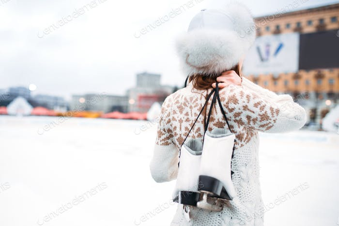 Young woman with skates in hands on skating rink
