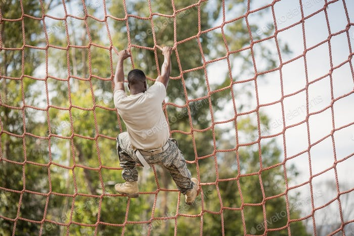 Military soldier climbing net during obstacle course