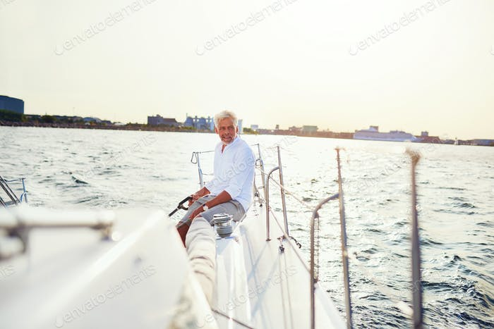 Mature man out sailing his yacht on a sunny afternoon